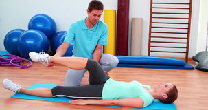 Εκπαιδευτής που βοηθά τον πελάτη του να κάμψει το πόδι της απόθεμα βίντεο
