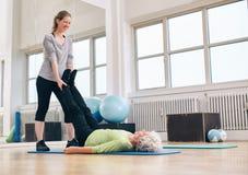 Εκπαιδευτής που βοηθά senior woman do leg τα τεντώματα Στοκ Φωτογραφία