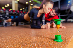 Εκπαιδευτής που εποπτεύει μια μυϊκή γυναίκα που κάνει τις ασκήσεις σανίδων, λουρί άσκησης Στοκ Εικόνα