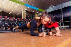 Εκπαιδευτής που εποπτεύει μια μυϊκή γυναίκα που κάνει τις ασκήσεις σανίδων, λουρί άσκησης Στοκ Φωτογραφία