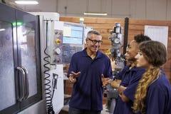 Εκπαιδευτικοί μαθητευόμενοι μηχανικών CNC στη μηχανή στοκ φωτογραφίες