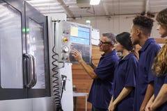 Εκπαιδευτικοί μαθητευόμενοι μηχανικών CNC στη μηχανή στοκ εικόνα με δικαίωμα ελεύθερης χρήσης