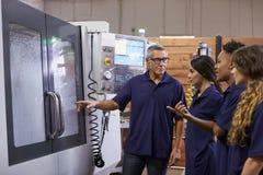 Εκπαιδευτικοί μαθητευόμενοι μηχανικών CNC στη μηχανή στοκ εικόνα