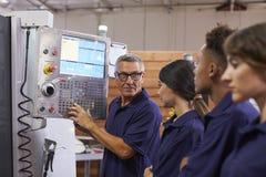 Εκπαιδευτικοί μαθητευόμενοι μηχανικών CNC στη μηχανή στοκ εικόνες