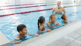 Εκπαιδευτικός ή λεωφορείο και ομάδα παιδιών που κάνουν τις ασκήσεις στην πισίνα απόθεμα βίντεο