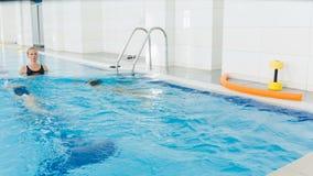 Εκπαιδευτικός και παιδί που κάνουν τις ασκήσεις στην πισίνα Το λεωφορείο διδάσκει τα κορίτσια για να κολυμπήσει απόθεμα βίντεο