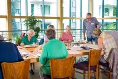 Εκπαιδευτικός που επιτηρεί τους σπουδαστές που χρωματίζουν στην κατηγορία Στοκ φωτογραφία με δικαίωμα ελεύθερης χρήσης