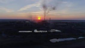 Εκπομπές στον αέρα, την άποψη κηφήνων των σωλήνων εργοστασίων με τον παχύ άσπρο καπνό στο ηλιοβασίλεμα υποβάθρου και την πόλη απόθεμα βίντεο