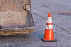 Εκσακαφέας με το ριγωτό πορτοκαλή κώνο κυκλοφορίας σε κάποια οδό στοκ εικόνα