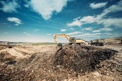 Εκσκαφέας που χρησιμοποιεί τη βαρέων καθηκόντων σέσουλα για τις οικοδομές στα απορρίματα dumpsite Στοκ εικόνα με δικαίωμα ελεύθερης χρήσης