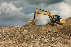 Εκσκαφέας σε ένα λατομείο που εξάγει την πέτρα για τον πιό πρόσφατο μετασχηματισμό στο αμμοχάλικο στοκ εικόνα