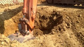 Εκσκαφέας στην εργασία backhoe το μηχανικό φτυάρι που λειτουργεί στον τομέα, σκάβει γύρω από τον κεντρικό στυλοβάτη απόθεμα βίντεο
