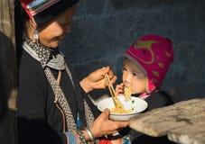 Εκτάριο Giang, Βιετνάμ - 14 Φεβρουαρίου 2016: Η μητέρα Hmong ταΐζει το γιο της με το στιγμιαίο νουντλς σε ήχο καμπάνας Van market Στοκ Εικόνα