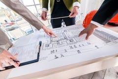Εκτίμηση του αρχιτεκτονικού σχεδίου Τρεις αρχιτέκτονες εξετάζουν Στοκ Φωτογραφίες