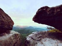 Εκτεθειμένος απότομος βράχος ψαμμίτη επάνω από τη βαθιά misty κοιλάδα στο τέλος του καλοκαιριού Ονειροπόλος διάθεση στοκ φωτογραφίες