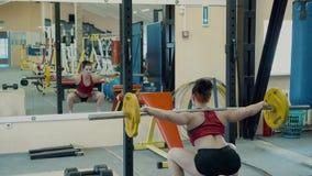 Νέο κορίτσι, αθλητικό, στη γυμναστική Εκτελεί μια άσκηση - καθίστε οκλαδόν με το barbell απόθεμα βίντεο