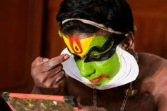 Εκτελεστής χορού Katakhali που κάνει το χρώμα προσώπου και makeup μπροστά από το χέρι - κρατημένος καθρέφτης στοκ εικόνες