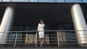 Εκτελεστική γυναίκα που εργάζεται με ένα κινητό τηλέφωνο στην οδό με το κτίριο γραφείων στο υπόβαθρο περπάτημα επιχειρηματιών απόθεμα βίντεο