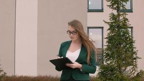 Εκτελεστική επιχειρησιακή γυναίκα με το φάκελλο που γράφει και που κάνει τη γραφική εργασία κοιτάζοντας γύρω από υπαίθρια απόθεμα βίντεο