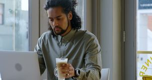 Εκτελεστικός έχοντας τον καφέ χρησιμοποιώντας το lap-top 4k απόθεμα βίντεο