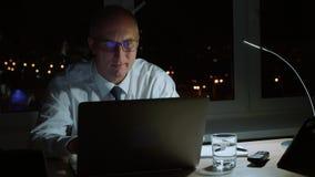 Εκτελεστικός επαγγελματικός διευθυντής που χαμογελά και workig με το lap-top αργά το βράδυ φιλμ μικρού μήκους