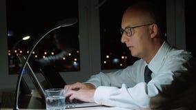 Εκτελεστικός επιχειρηματίας που χρησιμοποιεί το φορητό προσωπικό υπολογιστή απασχομένος στις υπερωρίες στο σκοτεινό γραφείο φιλμ μικρού μήκους