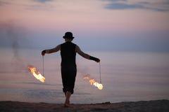 Εκτελεστής πυρκαγιάς πίσω με το κάψιμο POI στην παραλία Στοκ Εικόνα