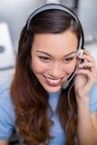 Εκτελεστική ομιλία εξυπηρέτησης πελατών χαμόγελου θηλυκή στην κάσκα στο γραφείο Στοκ Εικόνες