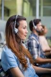 Εκτελεστική ομιλία εξυπηρέτησης πελατών χαμόγελου θηλυκή στην κάσκα στο γραφείο Στοκ εικόνες με δικαίωμα ελεύθερης χρήσης