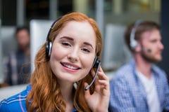 Εκτελεστική ομιλία εξυπηρέτησης πελατών χαμόγελου θηλυκή στην κάσκα στο γραφείο Στοκ Φωτογραφία