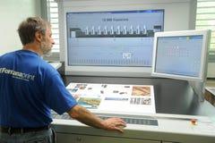 Εκτυπωτής που ελέγχει μια τυπωμένη ύλη που οργανώνεται στον πίνακα Στοκ φωτογραφία με δικαίωμα ελεύθερης χρήσης