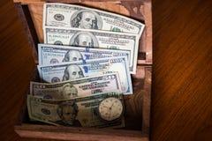 Εκτός από τα δολάρια ενώ συντήρηση στο ξύλινο κιβώτιο στοκ εικόνα