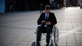Εκτός λειτουργίας συνεδρίαση επιχειρηματιών στην αναπηρική καρέκλα υπαίθρια και εργασία με το PC ταμπλετών απόθεμα βίντεο