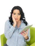 Εκφοβισμένη ανήσυχη ενδιαφερόμενη νέα ισπανική γυναίκα που κρατά μια ασύρματη ταμπλέτα στοκ εικόνες