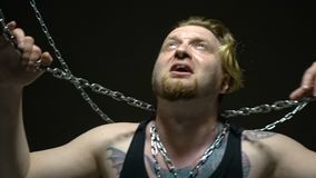 Εκφοβισμένος ξανθός φυλακισμένος που δεσμεύεται στις αλυσίδες απόθεμα βίντεο