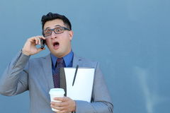 Εκφοβισμένο άτομο που μιλά στο τηλέφωνο που απομονώνεται σε ένα μπλε υπόβαθρο Στοκ φωτογραφία με δικαίωμα ελεύθερης χρήσης