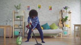 Εκφραστική θετική νοικοκυρά γυναικών αφροαμερικάνων νέα πολυάσχολη με την εργασία που σκουπίζει με ηλεκτρική σκούπα και χορός τρα φιλμ μικρού μήκους