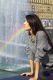 Εκφραστικοί αριθμοί παραγωγής. κορίτσι με το φωτεινό brunette makeup με μακρυμάλλη σε μια γκρίζα πηγή νερού ουράνιων τόξων ψεκασμο στοκ εικόνα