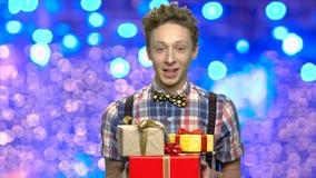 Εκφραστικός έφηβος με τα κιβώτια δώρων Χριστουγέννων απόθεμα βίντεο