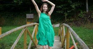Εκφραστικός χορός ενός νέου και όμορφου κοριτσιού σε μια ξύλινη γέφυρα απόθεμα βίντεο