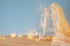 εκλεκτής ποιότητας άσπρη κορυφή δαντελλών τσιγγελακιών, μαργαριτάρια και θερμά φω'τα γιρλαντών Στοκ Φωτογραφία