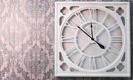 Εκλεκτής ποιότητας άσπρος χρόνος ρολογιών μετάλλων στο ρόδινο εκλεκτής ποιότητας τοίχο Στοκ Φωτογραφία
