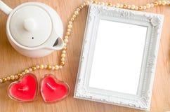 Εκλεκτής ποιότητας άσπρο πλαίσιο φωτογραφιών και κόκκινο κερί μορφής καρδιών στοκ εικόνα με δικαίωμα ελεύθερης χρήσης
