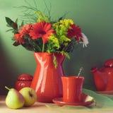 Εκλεκτής ποιότητας ακόμα ζωή με το κόκκινα επιτραπέζιο σκεύος, τα λουλούδια και τα φρούτα Στοκ φωτογραφία με δικαίωμα ελεύθερης χρήσης