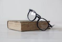 Εκλεκτής ποιότητας βιβλίο με τα μαύρα γυαλιά ανάγνωσης στην κορυφή Στοκ Εικόνες