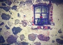 Εκλεκτής ποιότητας εικόνα των λουλουδιών στο παράθυρο, αρχαία πέτρα κτηρίου Στοκ Φωτογραφία
