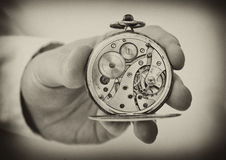 Το παλαιό ρολόι τσεπών εκμετάλλευσης χεριών παρουσιάζει μηχανισμό μηχανισμού. Στοκ Φωτογραφία