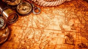 Εκλεκτής ποιότητας ενίσχυση - το γυαλί βρίσκεται σε έναν αρχαίο παγκόσμιο χάρτη Στοκ Φωτογραφία