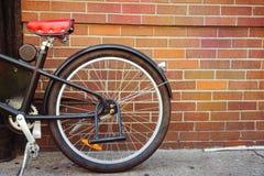 Εκλεκτής ποιότητας λεπτομέρεια ποδηλάτων πέρα από το υπόβαθρο τουβλότοιχος Στοκ Εικόνα