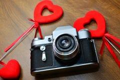Εκλεκτής ποιότητας κάμερα στον ξύλινο πίνακα με τις κόκκινες καρδιές Στοκ φωτογραφίες με δικαίωμα ελεύθερης χρήσης